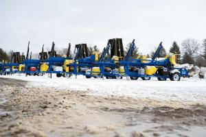 Image of several firewood processors lined up in the snow